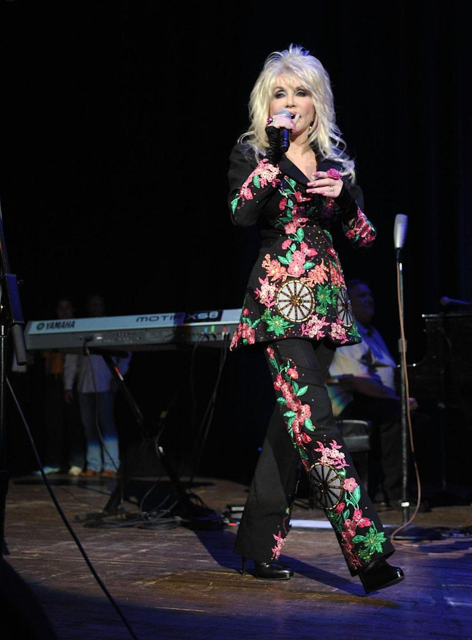 <p>Here, at a 2011 event with country singer-songwriter Marty Stuart, Dolly reimagines what the pantsuit can be with colorful beading in a botanical motif.</p>
