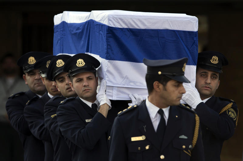 Members of the Knesset guard carry the coffin of late Israeli Prime Minister Ariel Sharon at the Knesset Plaza in Jerusalem, Monday, Jan. 13, 2014. Israel is holding a state memorial ceremony for the former Prime Minister Ariel Sharon at the country's parliament building. Monday's official ceremony in the Knesset in Jerusalem will be followed by a private burial on the family's desert ranch in southern Israel. (AP Photo/Bernat Armangue)