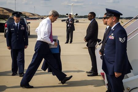 U.S. Secretary of State John Kerry (2nd L) looks down as he boards a plane to New Delhi at Andrews Air Force Base outside Washington July 29, 2014. REUTERS/Lucas Jackson