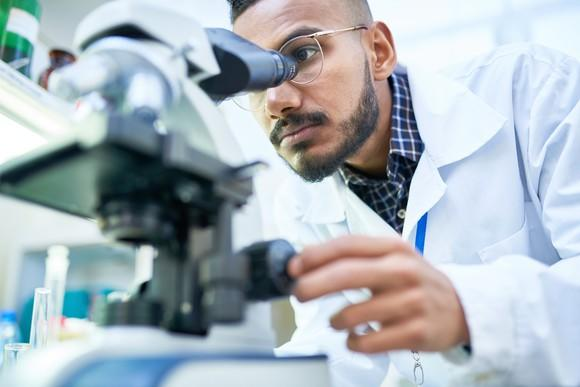 Man in a lab coat peering through a microscope.