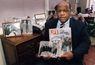 """Congressman John Lewis is seen in his Atlanta office with two of his favorite items from his collection of memorabilia from his younger days as a civil rights activist in the 1960s. He is holding a Life Magazine cover picturing the famous Selma march in 1965. (He is in this photo at front of the line of marchers.) He is also holding a photo of the 'Big Six' civil rights leaders of the time to plan for the famous March on Washington. The men in the photo are L to R: John Lewis, Whitney Young, A. Phillip Randolph, Martin Luther King, James Farmer, and Roy Wilkins. In background photos (picture at left) of Dr. Martin Luther King with Fred Shuttlesworth and Ralph Abernathy and Lewis with Robert Kennedy (picture at right)."""" (Atlanta Journal-Constitution via AP)"""