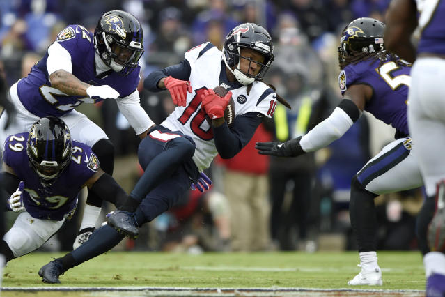 Houston Texans wide receiver DeAndre Hopkins (10) pushes forward after a catch as Baltimore Ravens free safety Earl Thomas (29), cornerback Jimmy Smith (22) and middle linebacker Josh Bynes (57) try to stop him during the first half of an NFL football game, Sunday, Nov. 17, 2019, in Baltimore. (AP Photo/Gail Burton)