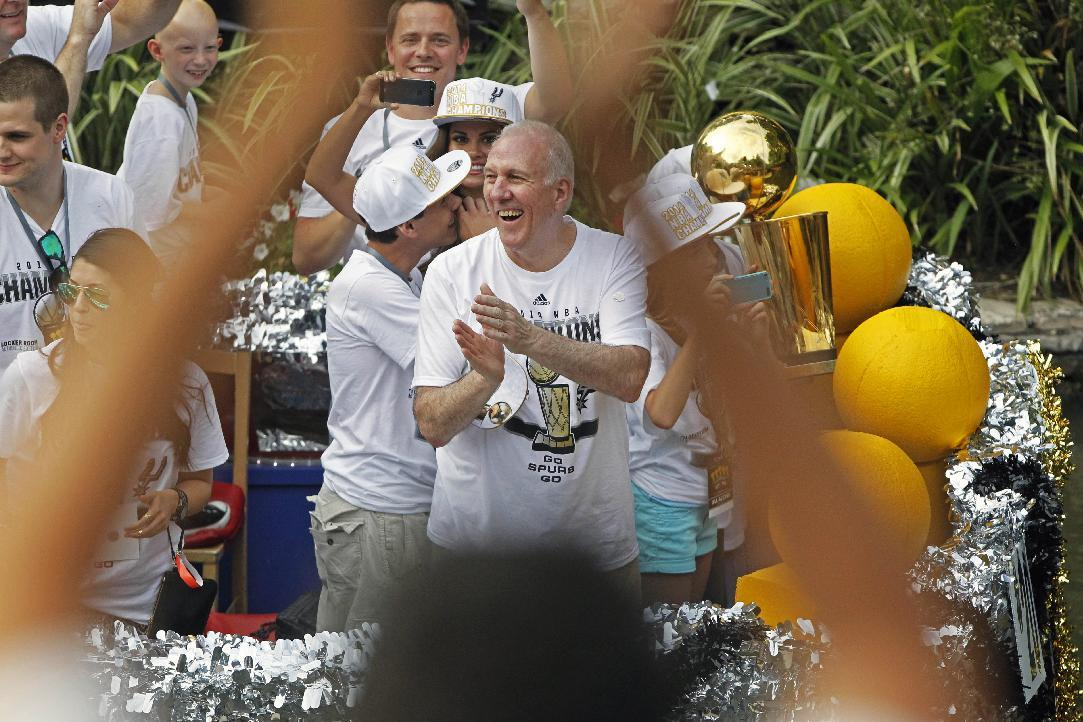 San Antonio Spurs head coach Gregg Popovich, center, claps during the basketball team's parade and celebration of their fifth NBA Championship, Wednesday,  June 18, 2014, in San Antonio. The Spurs defeated the Miami Heat for the title. (AP Photo/Michael Thomas)