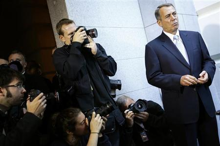 Photographers take pictures of U.S. House Speaker Boehner as he appears before reporters after a Republican caucus meeting at the U.S. Capitol in Washington