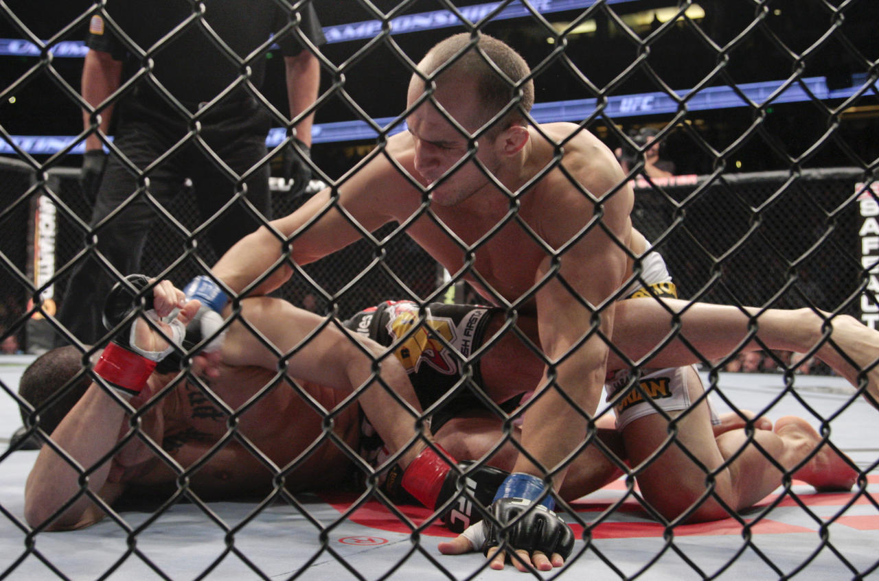 Junior dos Santos, right, of Brazil, takes down Cain Velasquez in the UFC mixed martial arts heavyweight title bout in Anaheim, Calif., Saturday, Nov. 12, 2011. Dos Santos won by knockout in the first round. (AP Photo/Jason Redmond)
