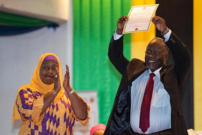 Vice President-elect Samia Suluhu (left) applauds as President-elect John Magufuli holds up his official certificate of victory in Dar es Salaam on October 30, 2015 (AFP Photo/Daniel Hayduk)