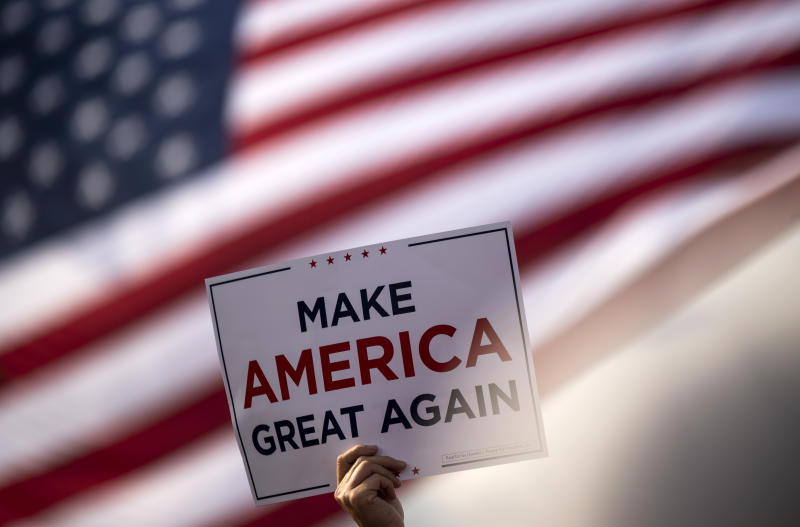 "BEMIDJI, MN - SEPTEMBER 18: A man waves a ""Make America Great Again"" sign before President Donald Trump arrives for a rally at the Bemidji Regional Airport on September 18, 2020 in Bemidji, Minnesota. Trump and challenger, Democratic presidential nominee and former Vice President Joe Biden, are both campaigning in Minnesota today. (Photo by Stephen Maturen/Getty Images)"