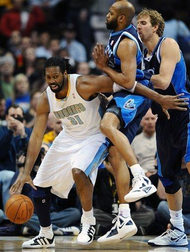 Denver Nuggets forward Nene (31), of Brazil, drives against Dallas Mavericks' Vince Carter, center, and Dirk Nowitzki, right, of Germany, in the first quarter of an NBA basketball game in Denver on Wednesday, Feb. 8, 2012. (AP Photo/Chris Schneider)