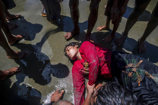 <p>A Rohingya Muslim woman, who crossed over from Myanmar into Bangladesh, lies unconscious on the shore of the Bay of Bangal after the boat she was traveling in capsized at Shah Porir Dwip, Bangladesh, Thursday, Sept. 14, 2017. (Photo: Dar Yasin/AP) </p>