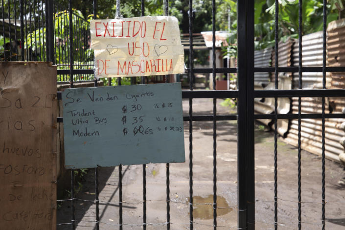A sign requiring the use of masks during the COVID-19 pandemic hangs over signs advertising cigarettes, eggs, matches, milk and coffee for sale on a gate at the entrance to a residential area in Managua, Nicaragua, Thursday, Sept. 9, 2021. (AP Photo/Miguel Andrés)