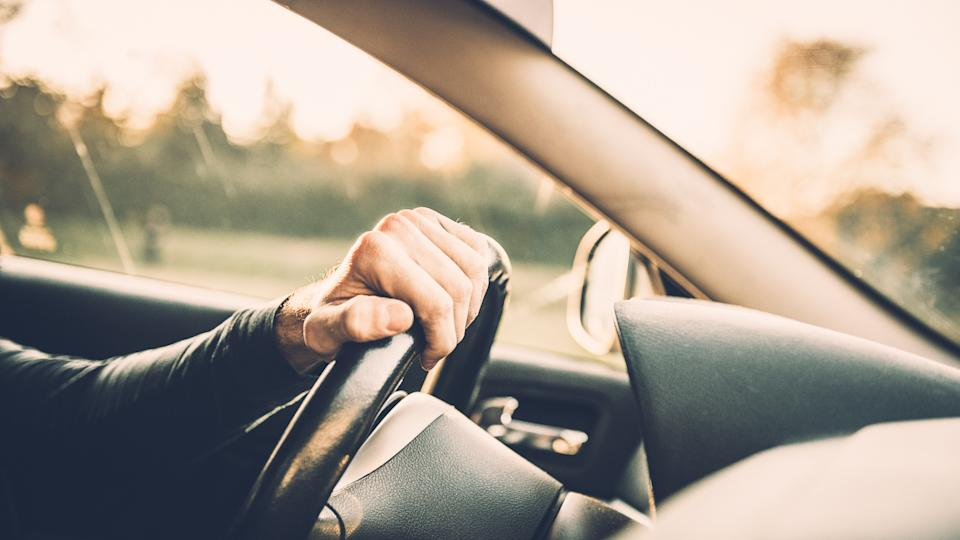 Man driving a car, close up on a steering wheel.