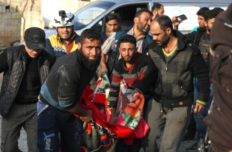 Residents and a rescue worker carry the body of a man killed in a reported Russian air strike in Kfar Ruma in Syria's northwestern Idlib province on November 10, 2019