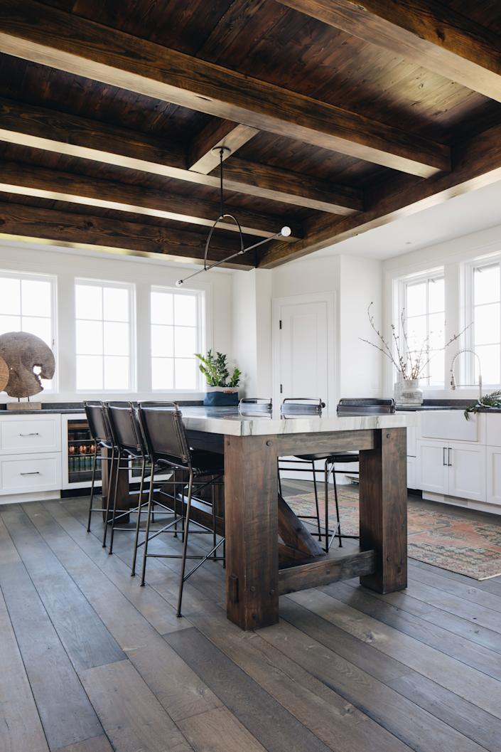 """<div class=""""caption""""> The Alabama wood that makes up the home's beams appears again in the kitchen table. <a href=""""https://fourhands.com/"""" rel=""""nofollow noopener"""" target=""""_blank"""" data-ylk=""""slk:Four Hands"""" class=""""link rapid-noclick-resp"""">Four Hands</a> counter stools and a <a href=""""https://katyskelton.com/"""" rel=""""nofollow noopener"""" target=""""_blank"""" data-ylk=""""slk:Katy Skelton"""" class=""""link rapid-noclick-resp"""">Katy Skelton</a> light add to the ambience. The rug and baskets are from <a href=""""https://amystormandco.com/"""" rel=""""nofollow noopener"""" target=""""_blank"""" data-ylk=""""slk:Amy Storm & Company"""" class=""""link rapid-noclick-resp"""">Amy Storm & Company</a>. </div>"""