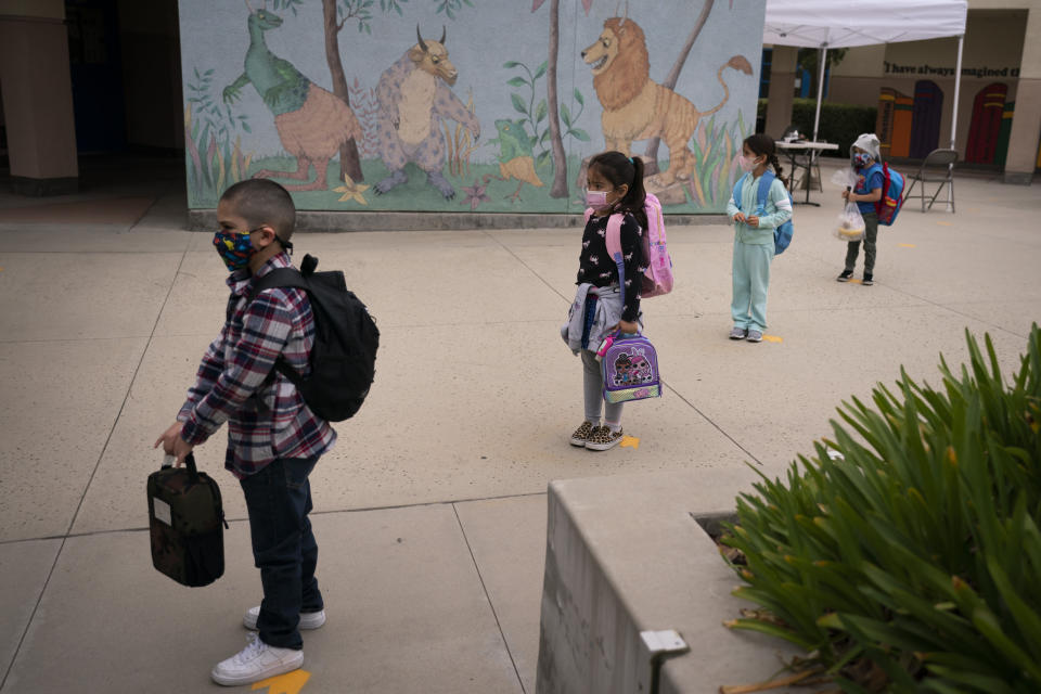 FILE — In this April 13, 2021 file photo socially distanced kindergarten students wait for their parents to pick them up on the first day of in-person learning at Maurice Sendak Elementary School in Los Angeles, Tuesday, April 13, 2021. California schools have a few statewide requirements for how schools apply COVID rules for schools but leave most details up to the local districts, leading to a dizzying patchwork of approaches that parents and teachers say can be confusing and frustrating. (AP Photo/Jae C. Hong, File)