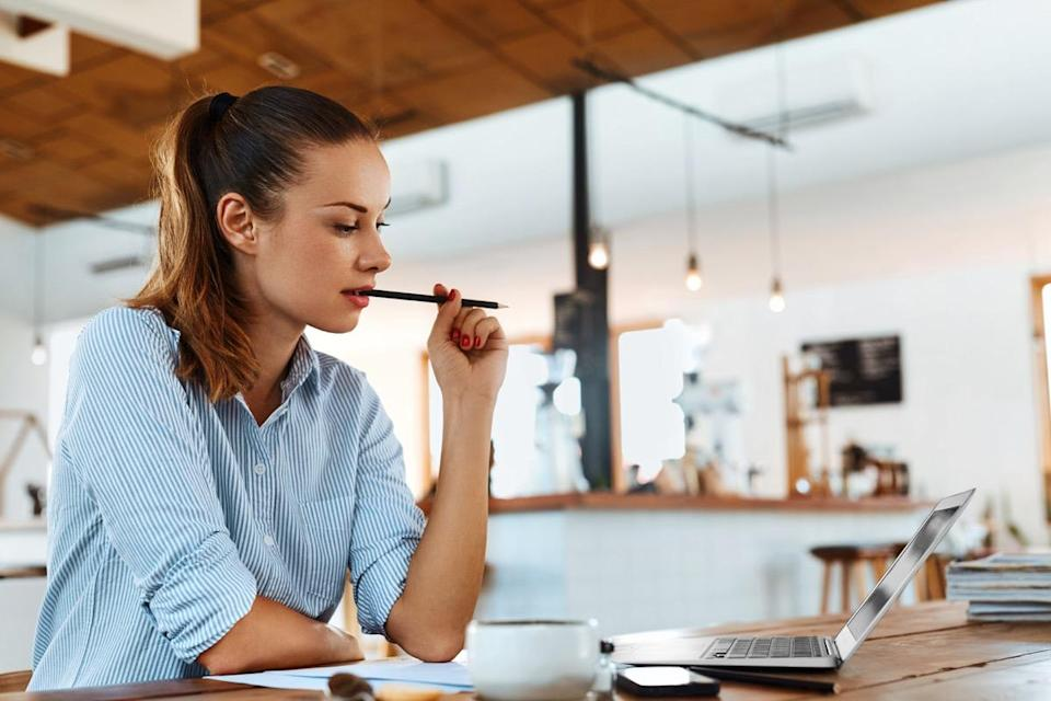 Freelancer Woman Using Laptop Computer Sitting At Cafe Table