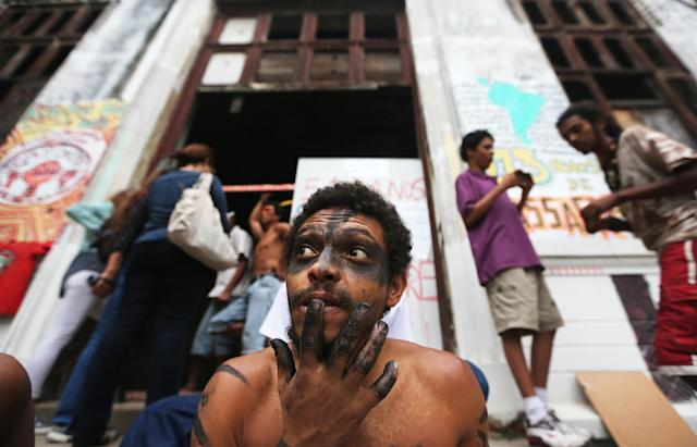 RIO DE JANEIRO, BRAZIL - OCTOBER 17: Members and supporters of an indigenous community gather in front of the Aldeia Maracana building they are occupying next to Maracana Stadium, the site of the 2014 World Cup final, on October 17, 2013 in Rio de Janeiro, Brazil. The fading structure used to house the Museum of Indian Culture before deteriorating and becoming occupied by squatting indigenous members in 2006. The building was slated for destruction ahead of the 2014 World Cup and the community was forcibly evicted in March. However, the community has managed to return and thus far have successfully battled to save the structure, which they hope to convert into an indigenous university. Indigenous groups throughout Brazil are battling the Brazilian government over land rights and other issues. (Photo by Mario Tama/Getty Images)