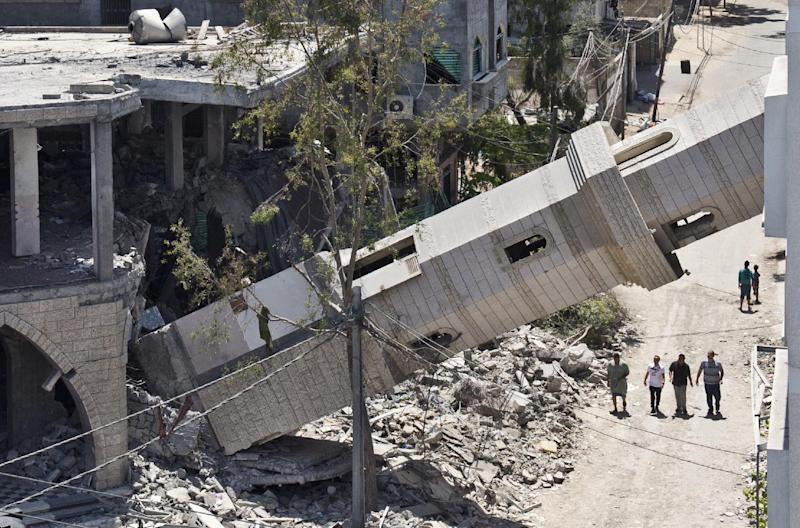 A picture taken on August 22, 2014 shows four Palestinian men walking under the toppled minaret of a mosque in Gaza City which was almost completely destroyed in an Israeli airstrike weeks ago