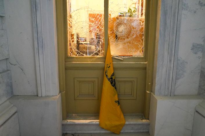 """A flag hangs between broken windows after supporters of President Donald Trump tried to break through police barriers outside the Capitol on Jan 6.<span class=""""copyright"""">John Minchillo—AP</span>"""