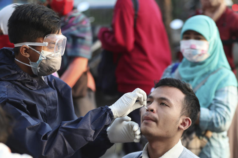 A health worker conducts a swab test for the new coronavirus at train station in Bekasi on the outskirts of Jakarta, Indonesia, Tuesday, May 5, 2020. (AP Photo/Achmad Ibrahim)