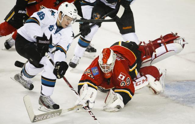 San Jose Sharks' Tomas Hertl, left, from the Czech Republic, tries to get the puck past a diving Calgary Flames goalie Reto Berra, from Switzerland, during the second period of an NHL hockey game Tuesday, Nov. 12, 2013, in Calgary, Alberta. (AP Photo/The Canadian Press, Jeff McIntosh)
