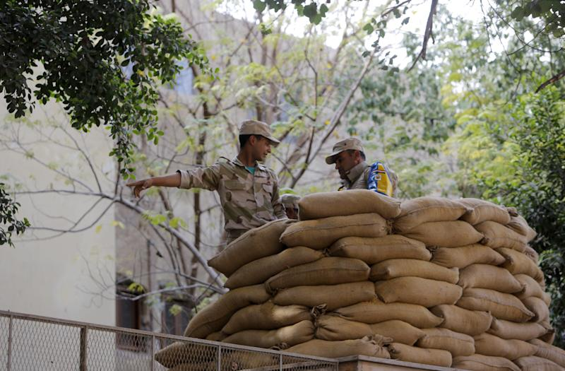 "Egyptian army soldiers install a protective barrier of sand bags outside a polling station in Cairo, Egypt, Monday, Jan. 13, 2014. The January 14-15 vote on the draft constitution will be the first real test of the post-Morsi regime. A comfortable ""yes"" vote and a respectable turnout would be seen as bestowing legitimacy, while undermining the Islamists' argument that Morsi remains the nation's elected president. (AP Photo/Amr Nabil)"