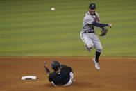 Atlanta Braves shortstop Dansby Swanson, right, throws to first to attempt a double play as Miami Marlins' Jesus Aguilar, left, is out at second during the eighth inning of a baseball game, Saturday, June 12, 2021, in Miami. Marlins' Adam Duvall was safe at first. (AP Photo/Wilfredo Lee)