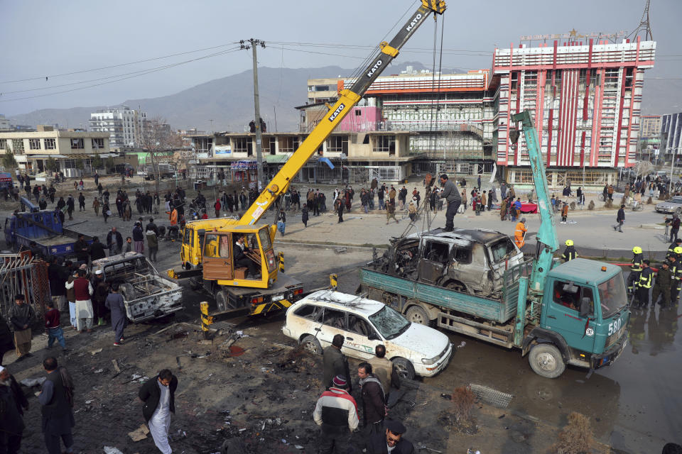Afghan security personnel oversee the removal of damaged vehicles after a bombing attack in Kabul, Afghanistan, Sunday, Dec. 20, 2020. Afghanistan's Interior Ministry says that the car bomb blast that has hit the Afghan capital has killed at least eight people and wounded more than 15 others, including a member of parliament, Khan Mohammad Wardak. (AP Photo/Rahmat Gul)