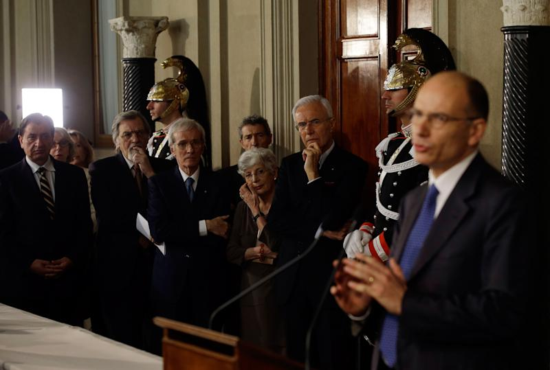 """Qurinale Presidential palace personnel listen to Italian Democratic Party lawmaker Enrico Letta, right, making his statement to the media after talks with Italian President Giorgio Napolitano, in Rome's Quirinale presidential palace, Wednesday, April 24, 2013. Italy's president has appointed Enrico Letta as premier, asking him to try to form a government to end Italy's political paralysis and set the country back on the path of reform and economic growth. Letta, a 46-year-old longtime center-left lawmaker, told reporters Wednesday he accepted the job knowing it's an enormous responsibility and that Italy's political class """"has lost all credibility."""" (AP Photo/Gregorio Borgia)"""