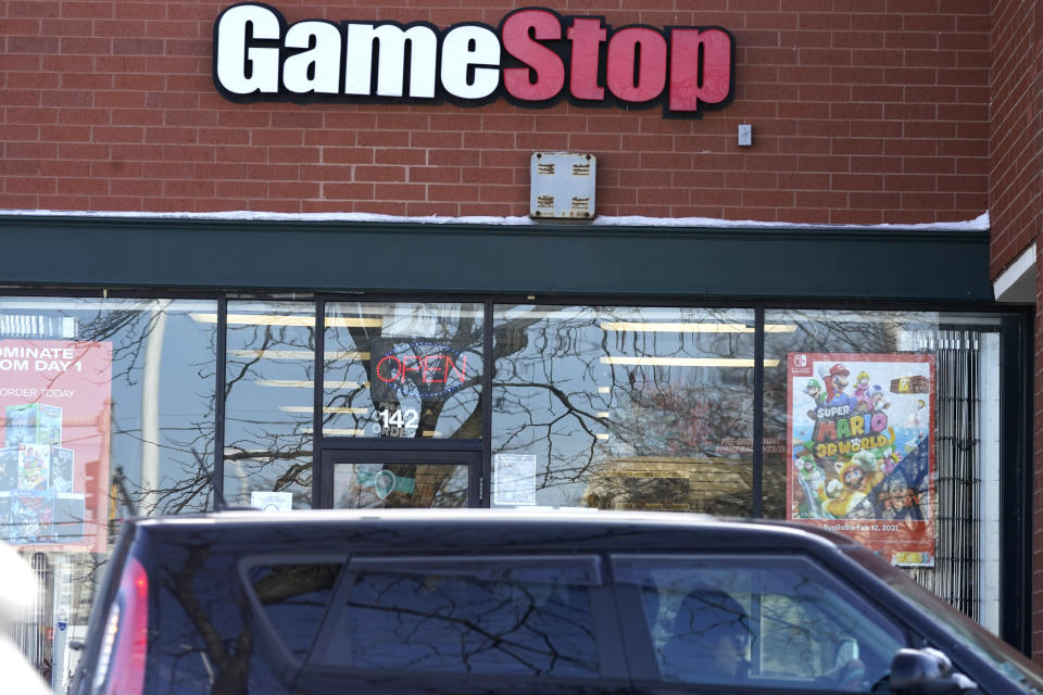 A vehicle passes in front of a GameStop store in Vernon Hills, Ill., Thursday, Jan. 28, 2021. The online trading platform Robinhood is moving to restrict trading in GameStop and other stocks that have soared recently due to rabid buying by smaller investors. GameStop stock has rocketed from below $20 earlier this month to close around $350 Wednesday as a volunteer army of investors on social media challenged big institutions who had placed market bets that the stock would fall. (AP Photo/Nam Y. Huh)