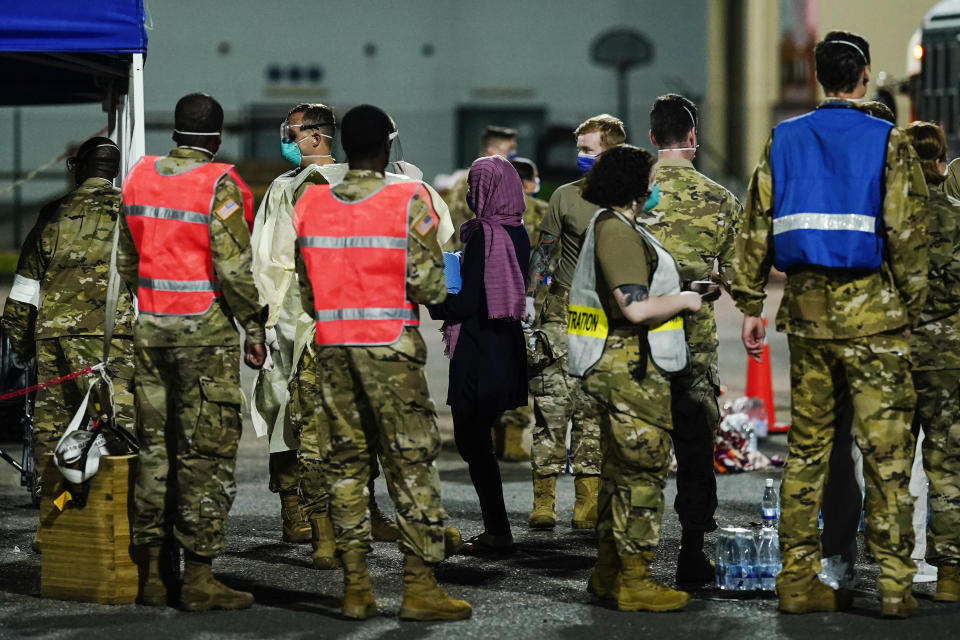 People flown out of Afghanistan leave a transport bus at Ramstein Air Base and are met by soldiers and helpers, in Ramstein-Miesenbach, Germany, Friday, Aug. 20, 2021. (Uwe Anspach/dpa via AP)