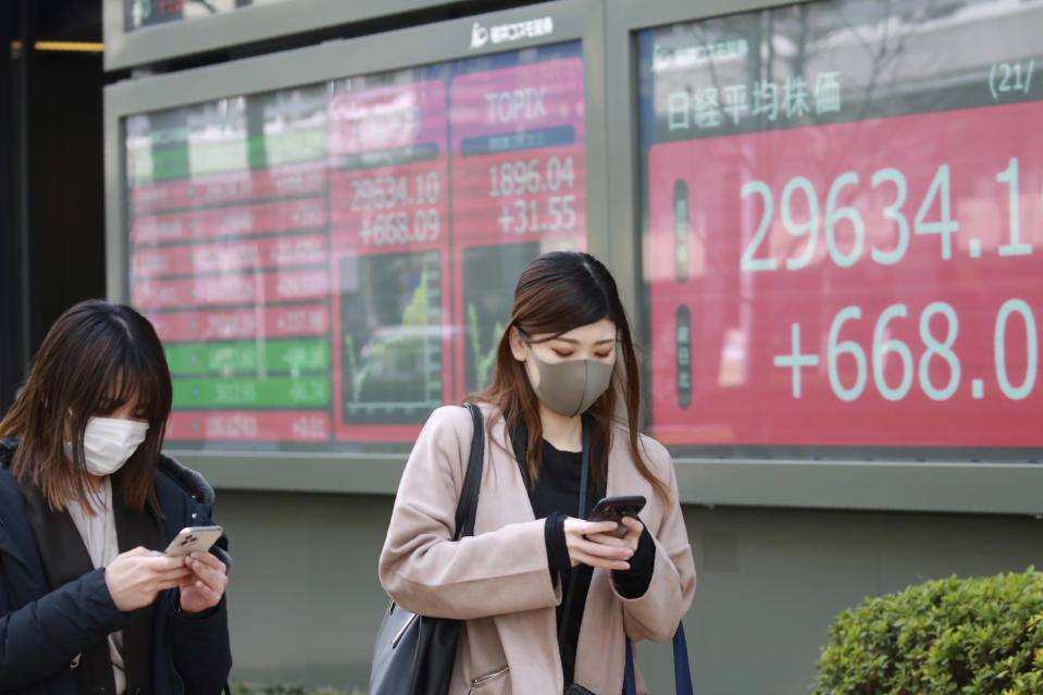 People walk by an electronic stock board of a securities firm in Tokyo, Monday, March 1, 2021. Asian shares were higher on Monday on hopes for President Joe Biden's stimulus package and bargain-hunting buying after the shares' fall last week. (AP Photo/Koji Sasahara)
