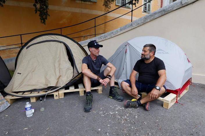 Thierry Paysant, a security worker and firefighter at the Pasteur hospital, and Christophe, a carer at the same hospital, sit in front of their tents near the Abbaye Saint-Pons in Nice during a hunger strike to protest against France's restrictions, including compulsory health passes (REUTERS)