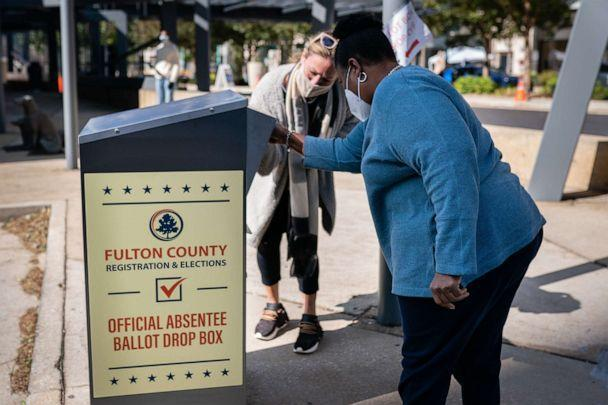 PHOTO: An election observer assists a voter as she drops off an absentee ballot into a drop box outside a polling location for the 2020 Presidential election in Atlanta, on Nov. 3, 2020. (Elijah Nouvelage/Bloomberg via Getty Images, FILE)