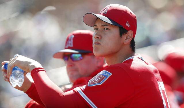 Los Angeles Angels' Shohei Ohtani stands in the dugout during the first inning of a spring training baseball game against the San Diego Padres, Monday, Feb. 26, 2018, in Peoria, Ariz. (AP Photo/Charlie Neibergall)