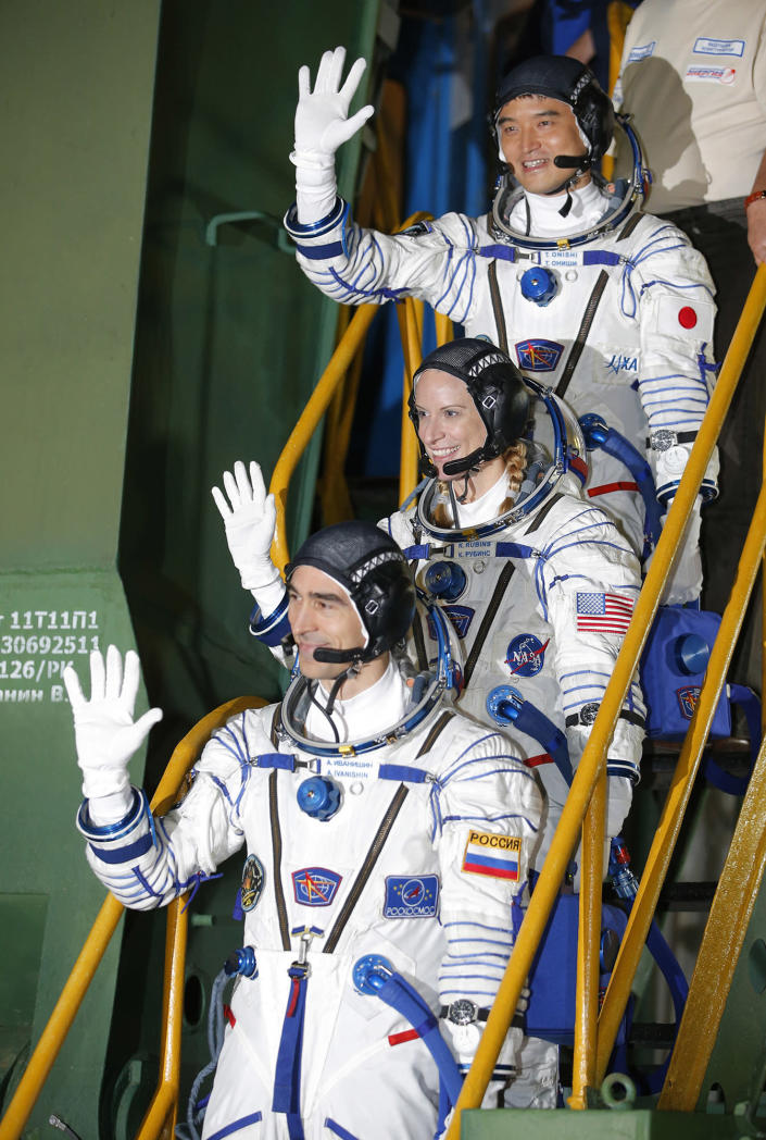 <p>U.S. astronaut Kate Rubins, center, Russian cosmonaut Anatoly Ivanishin, bottom, and Japanese astronaut Takuya Onishi, members of the main crew of the mission to the International Space Station (ISS), gesture close to the rocket prior the launch at the Russian leased Baikonur cosmodrome, Kazakhstan, Thursday, July 7, 2016. (AP Photo/Dmitri Lovetsky, Pool) </p>