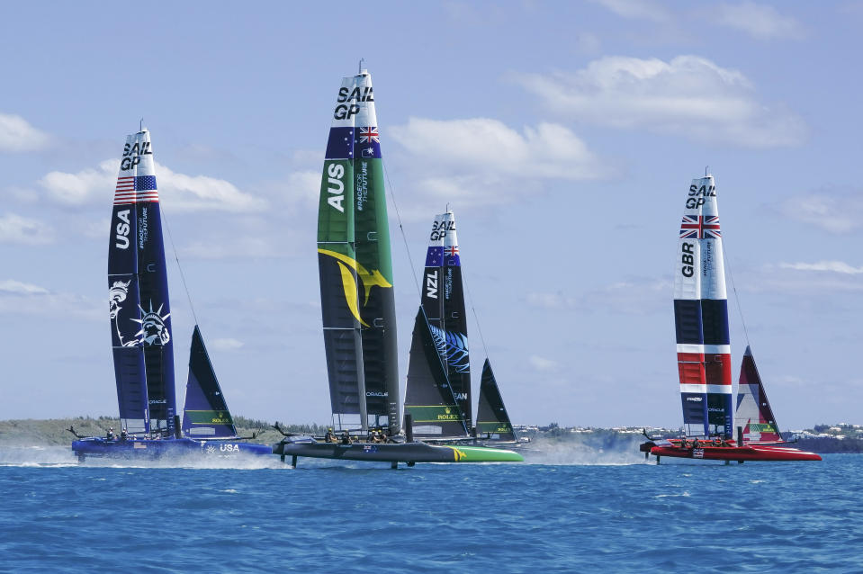 In this photo provided by SailGP, from left to right, the USA, Australia, New Zealand and Britain SailGP teams compete during the Bermuda SailGP in Hamilton, Bermuda, on Friday, April 23, 2021. Skipper Tom Slingsby and defending champion Team Australia won all three fleet races Friday on Bermuda's Great Sound in an impressive performance on the first day of the second season of the SailGP global league. (Thomas Lovelock/SailGP via AP)