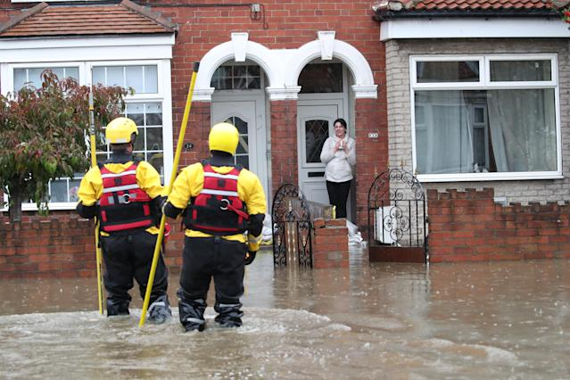Fire and Rescue service members walk through flood water in Doncaster. (PA)