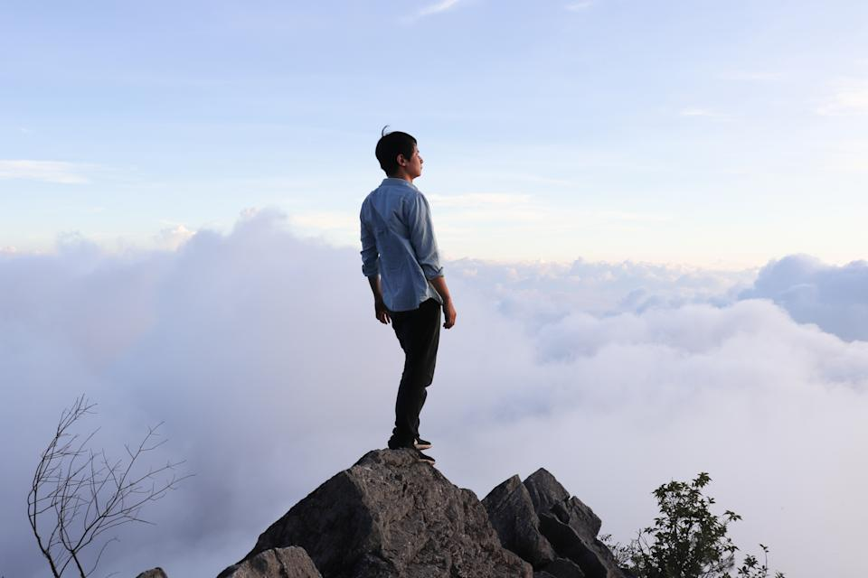 Asian man standing on the hilltop.