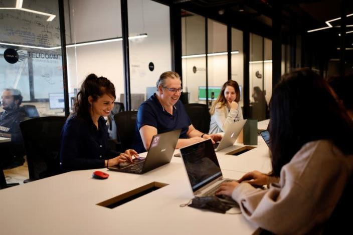Neta Schreiber, CEO and Co-Founder at SafeUP, a women's safety net application, works with her team members at a co-working space in Tel Aviv