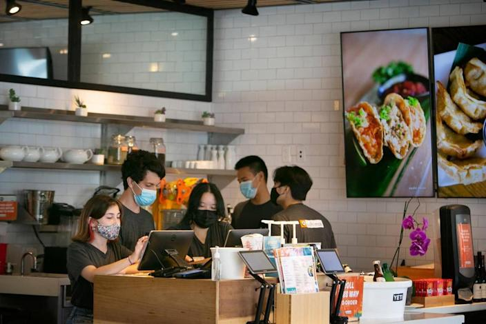 Mary Catherine Lorié, 19, works the cash register as fellow teen employees Dave Buitrago, 18; Samantha Su, 19; Kyle Ng, 16; and Michael Concordia, 19, work beside her at the Sushi Maki in Dadeland.