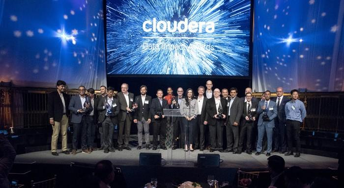Screen showing Cloudera logo above group of 20 people on a stage.
