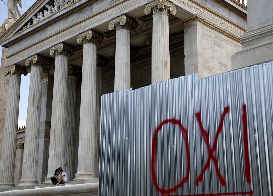 A NO graffiti is seen as Japanese tourists sit at the entrance of the Athens Academy, Greece, July 4, 2015. With less than 24 hours to go until a referendum on the conditions of a new bailout deal, Greek officials prepare polling stations, as the latest opinion polls show 'Yes' and 'No' sides neck-and-neck. REUTERS/Yannis Behrakis