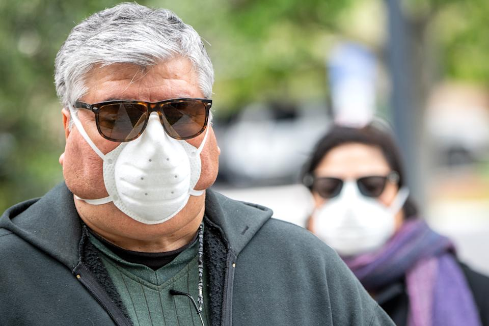 Overweight hispanic or middle eastern senior couple wearing a N95 protective mask due Covid-19 pandemic