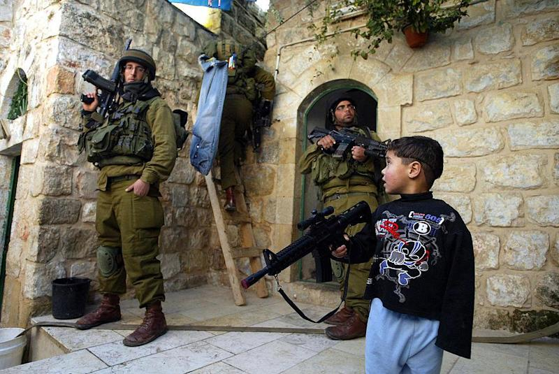 A Palestinian boy plays with his plastic rifle as Israeli soldiers search homes and rooftops in the West Bank town of Hebron in this file photo from 29 December 2006: AFP/Getty Images