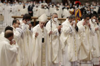 Pope Francis tells newly ordained priests to remove their face masks, used to curb the spread of COVID-19, for a group photo at the end of their ordination ceremony, inside St. Peter's Basilica, at the Vatican, Sunday, April 25, 2021. (AP Photo/Andrew Medichini)