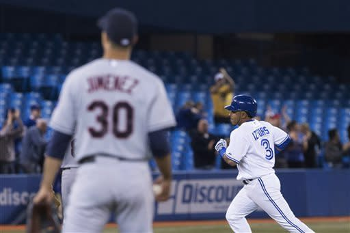 Toronto Blue Jays' Maicer Izturis, right, rounds the bases after he homers to right off a pitch from the Cleveland Indians' Ubaldo Jimenez (30) during the third inning of a baseball game in Toronto on Wednesday, April 3, 2013. (AP Photo/The Canadian Press, Chris Young)