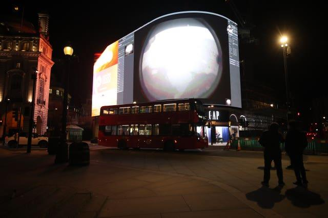 The landing being live streamed on Piccadilly Lights in central London