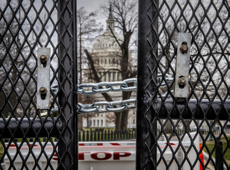 WASHINGTON, DC - January 08:  The U.S. Capitol is visible through a gap in the tall new fencing erected in the wake of the looting on Wednesday, in Washington, DC on January 08.  (Photo by Bill O'Leary/The Washington Post via Getty Images)