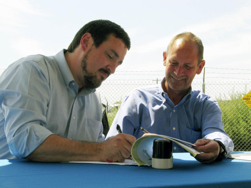 Washington Ecology Director Ted Sturdevant,  left, and Pacific Northwest Regional Director Karl Wirkus of the U.S. Bureau of Reclamation sign an agreement, Tuesday, Aug. 2, 2011 near Moses Lake, Wash. to provide new water supplies for as many as 100 communities and irrigators in Eastern Washington. (AP Photo/Shannon Dininny)