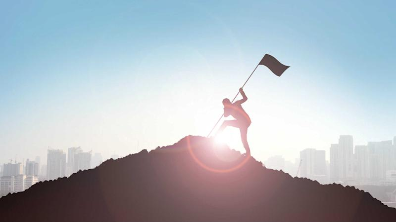 Planting a flag at the top of a mountain